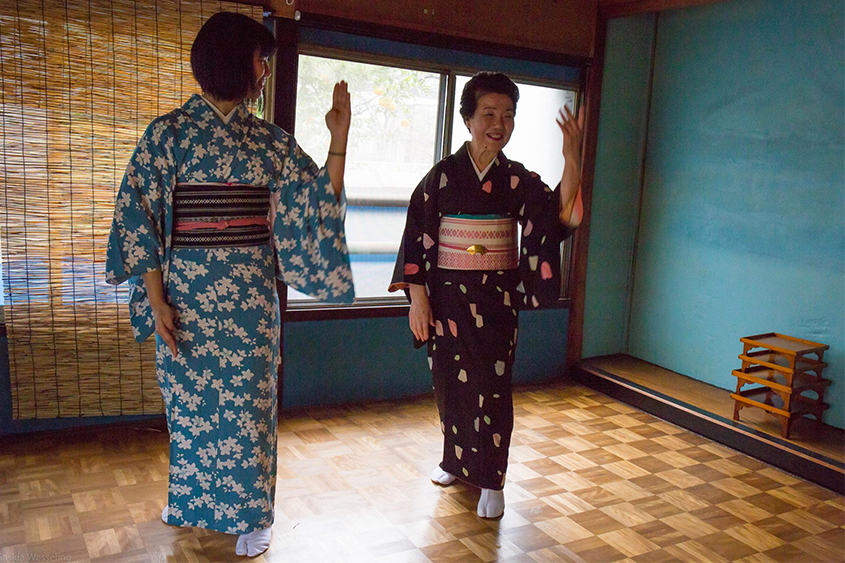 An older Fukagawa geisha helping a new Fukagawa trainee with her dance lessons