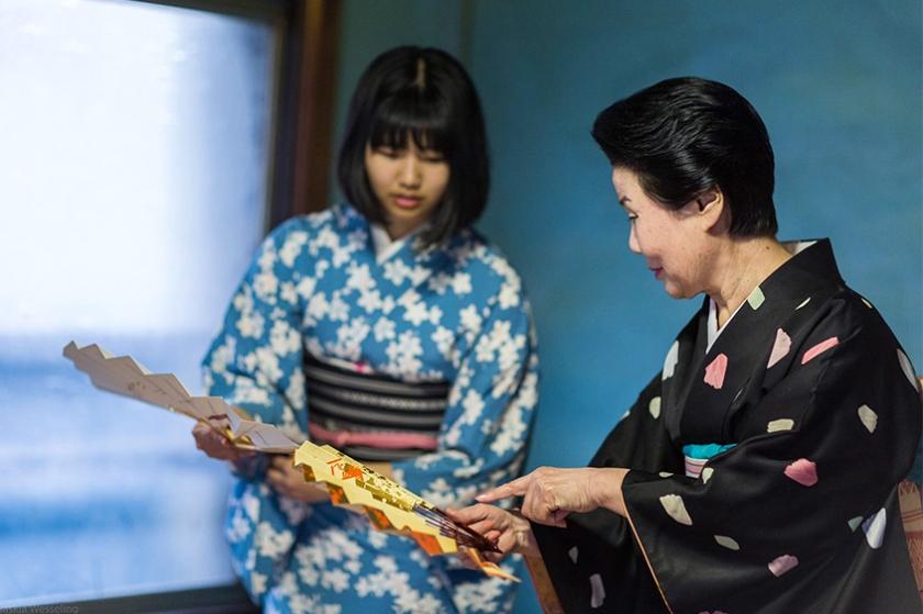 An older Fukagawa geisha helping a new Fukagawa trainee with her lessons